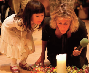 Elder, Gigi Coyle, along with Findhorn community child, Aayana Ito, blow out the Summit candle with a blessing for the children.
