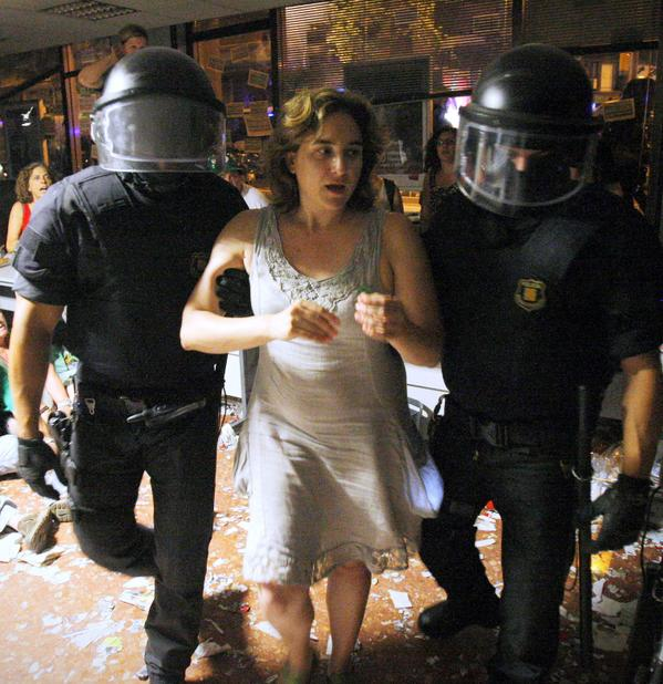 Ada Colau is escorted out by riot police officers after occupying a bank in Barcelona, Spain in 2013. Now she is Barcelona's next Mayor.